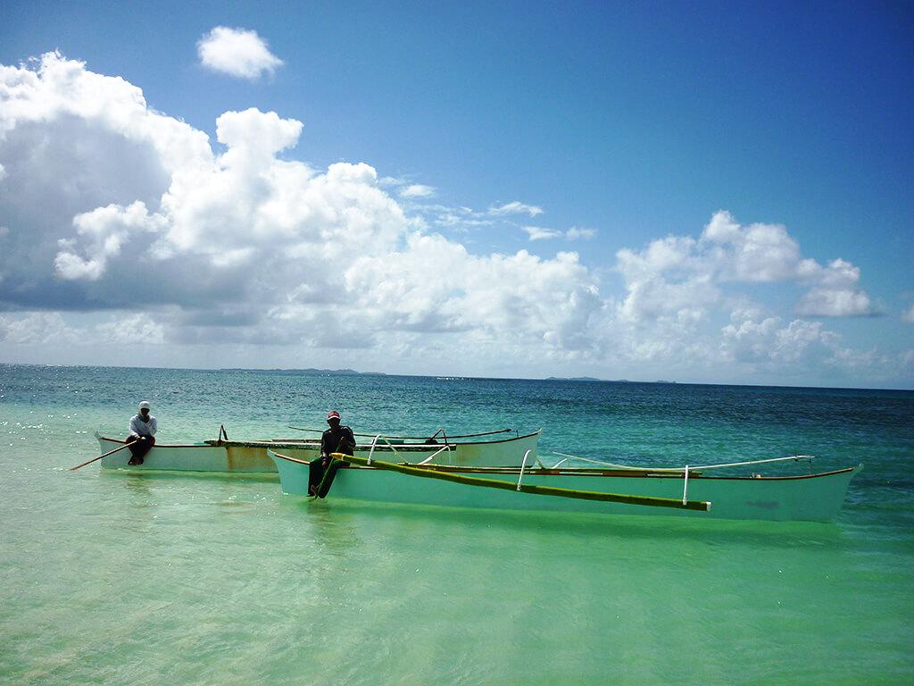 Bateau de pêche sur l'eau turquoise aux Philippines.