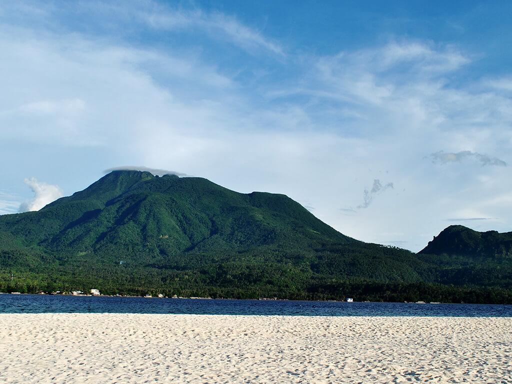 Vue sur les Montagnes depuis la plage de sable blanc dans les régions Camiguin et Siargao.