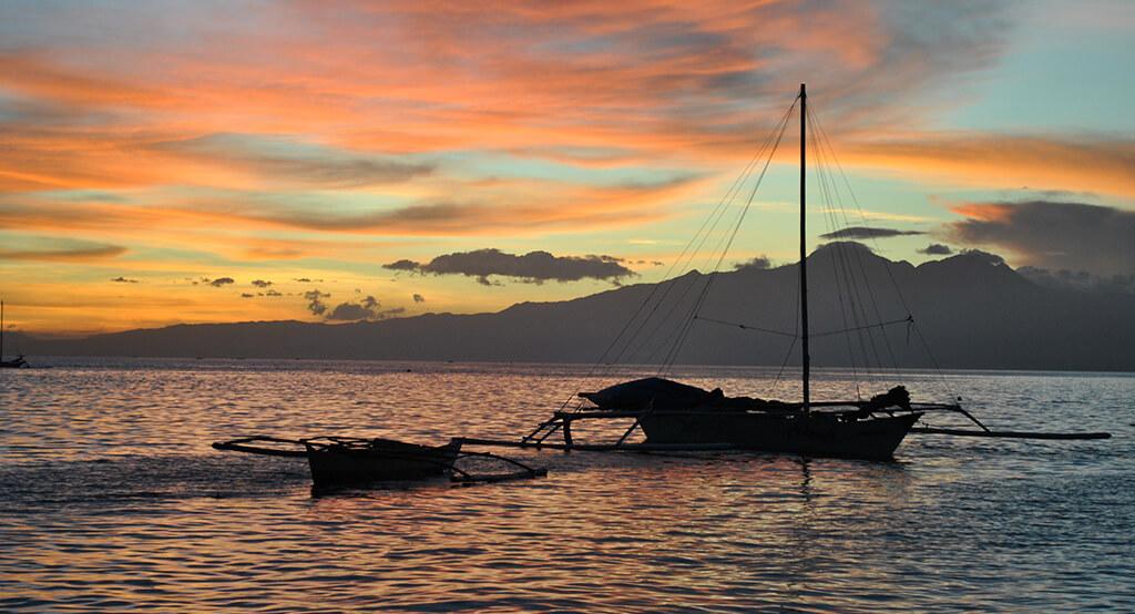 Coucher de soleil sur la mer avec un bateau à Siquijor.